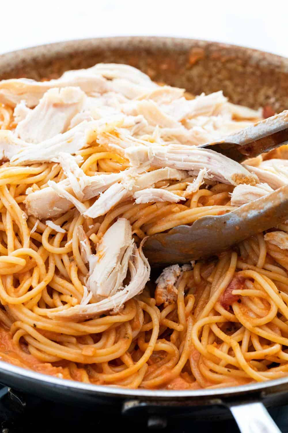 Shredded chicken on top of pasta
