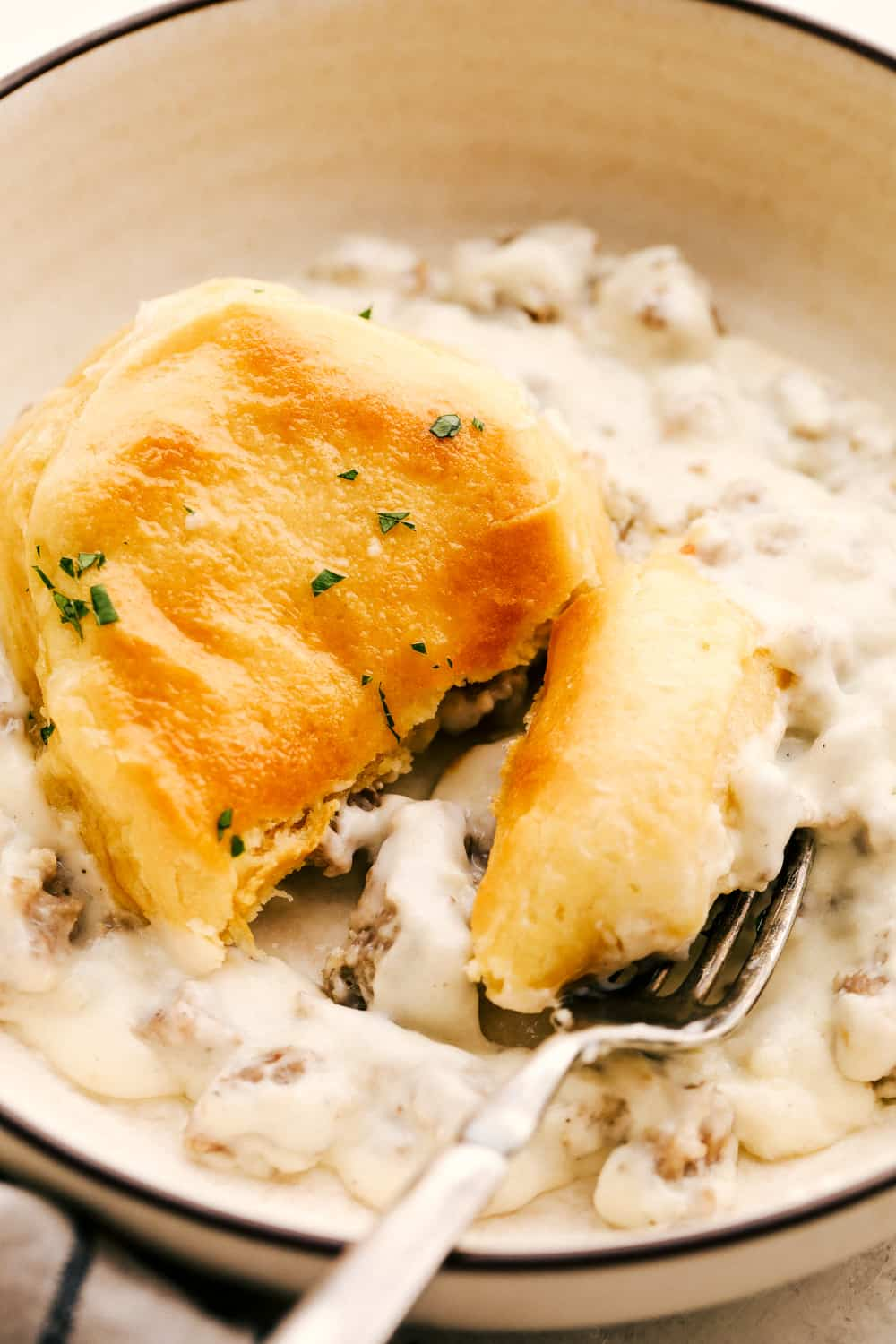 Golden flakey biscuits with savory rich sausage gravy on a plate.