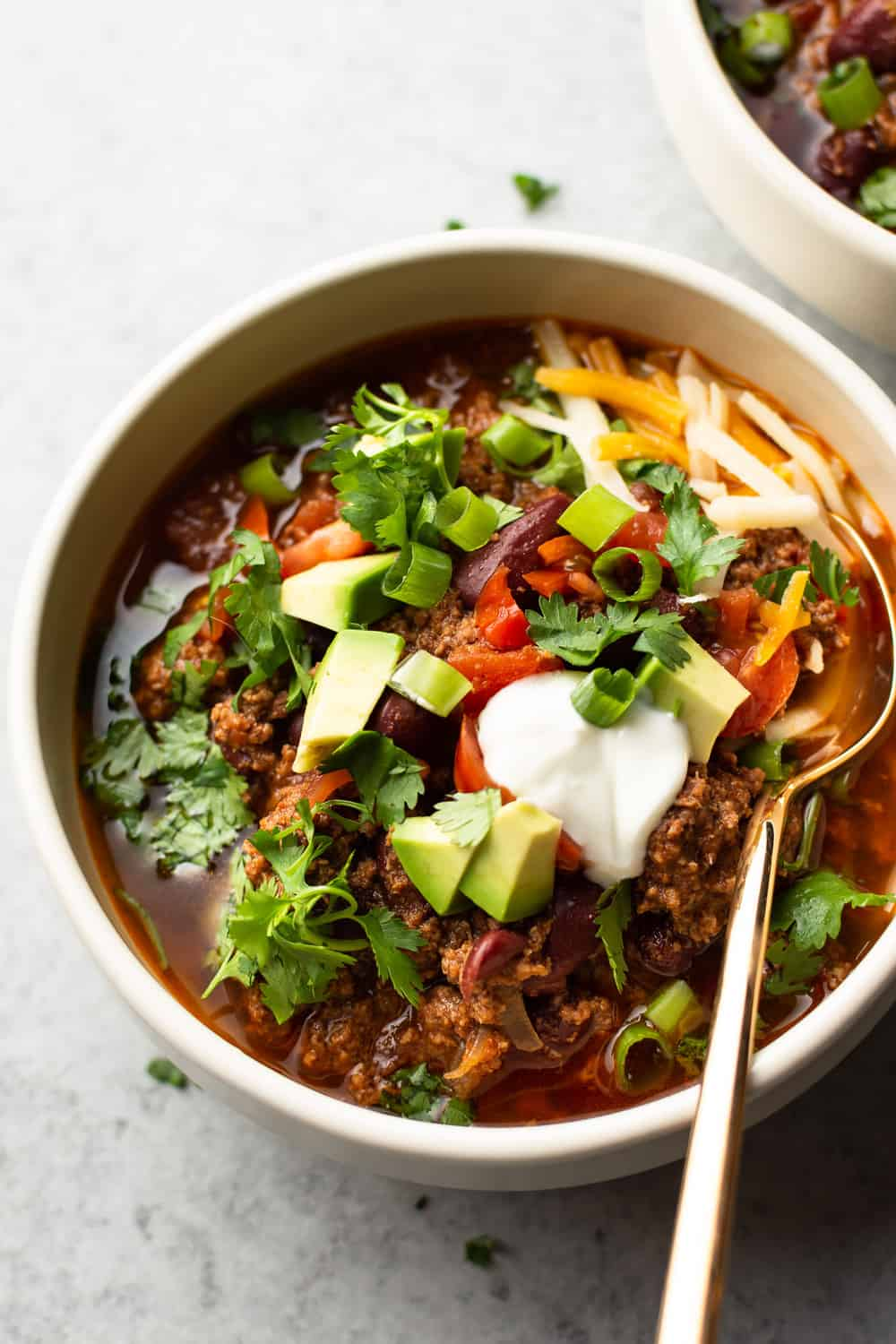 Instant Pot chili in a bowl with a gold spoon