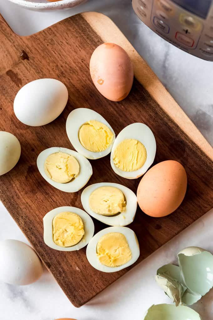 Sliced hard boiled eggs on a wooden cutting board.