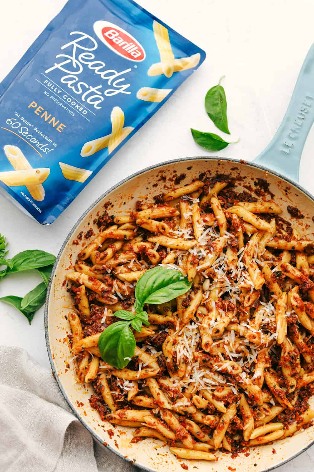 Sun dried tomato pesto pasta in a skillet with a package of ready pasta.