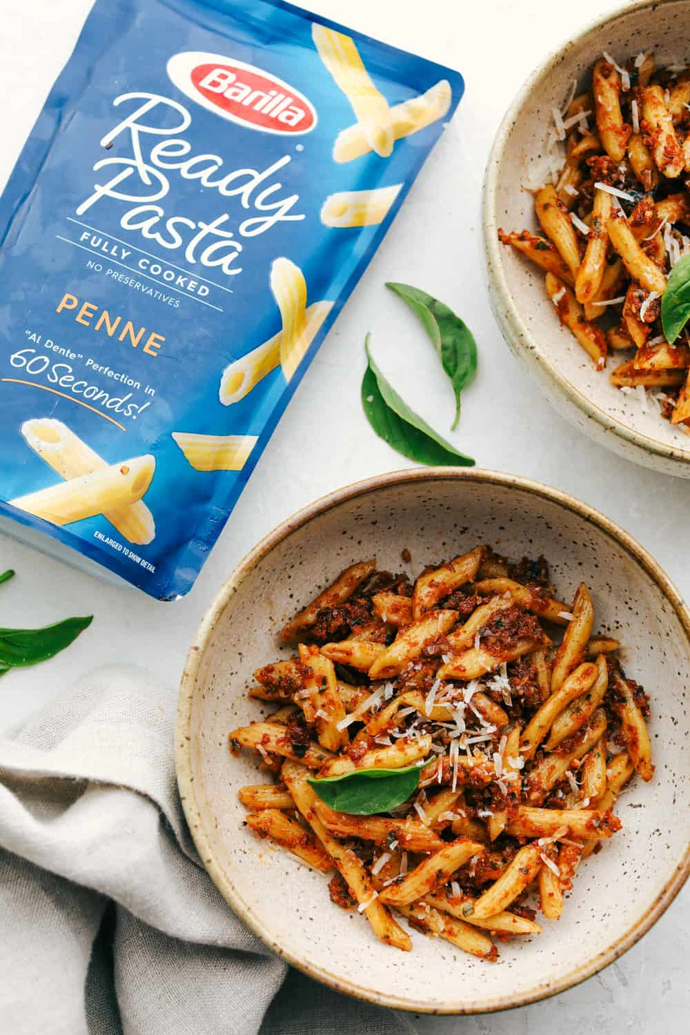 Sun dried tomato pesto pasta in a bowl with the barilla ready pasta on the side in the bag.