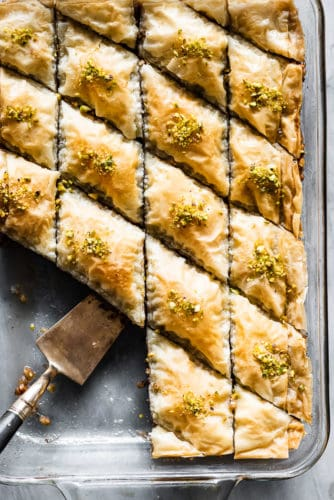 Baklava in a pan with a serving spoon.