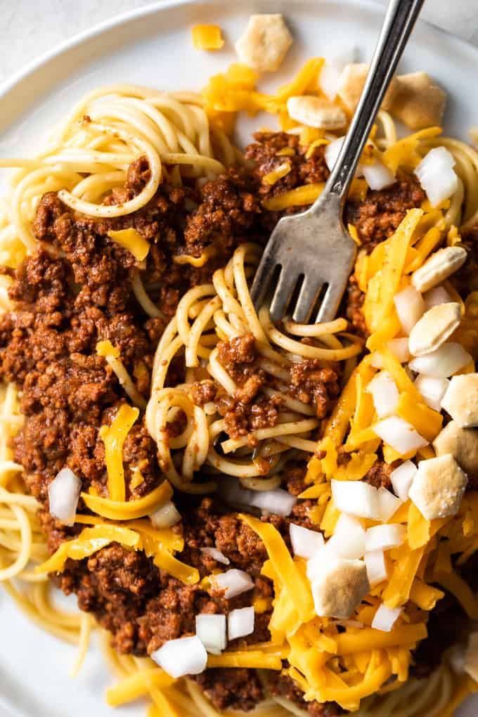 Cincinnati chili with spaghetti noodles garnished with cheese, onions and crackers.