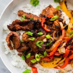 Korean Beef Bulgogi served over rice in a bowl with grilled onions and bell peppers