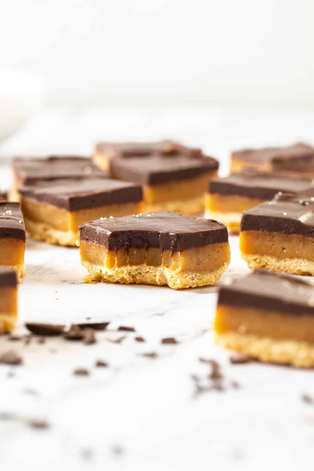 Closeup of a slice of millionaire shortbread with a bite mark in it