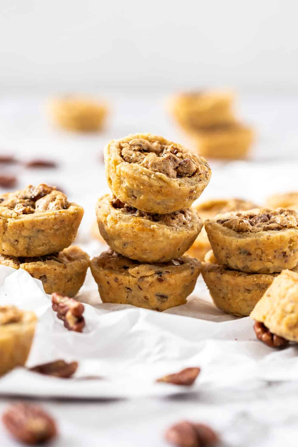 Small stacks of pecan tassies on a sheet of baking paper