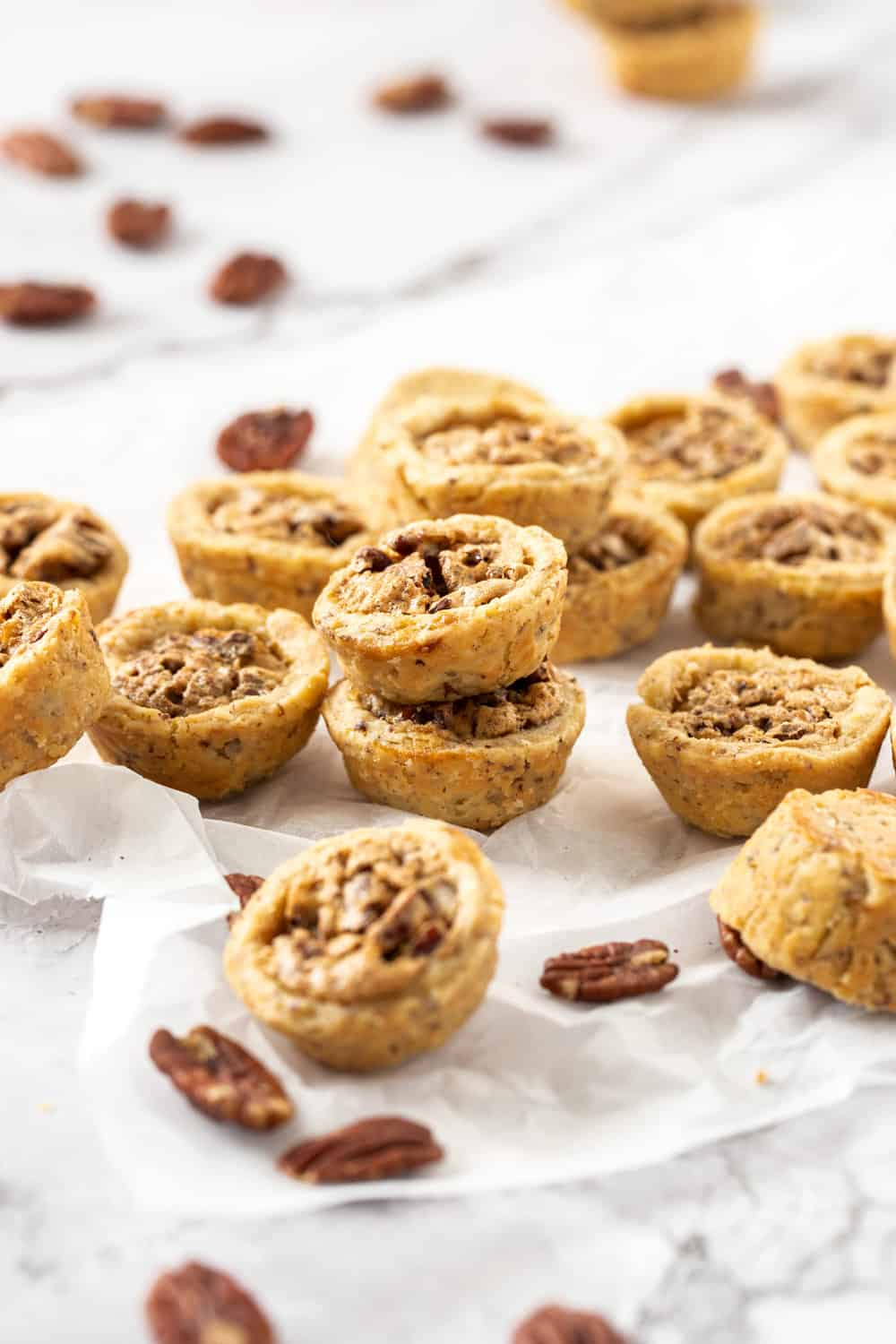 A pile of pecan tassies on a sheet of baking paper