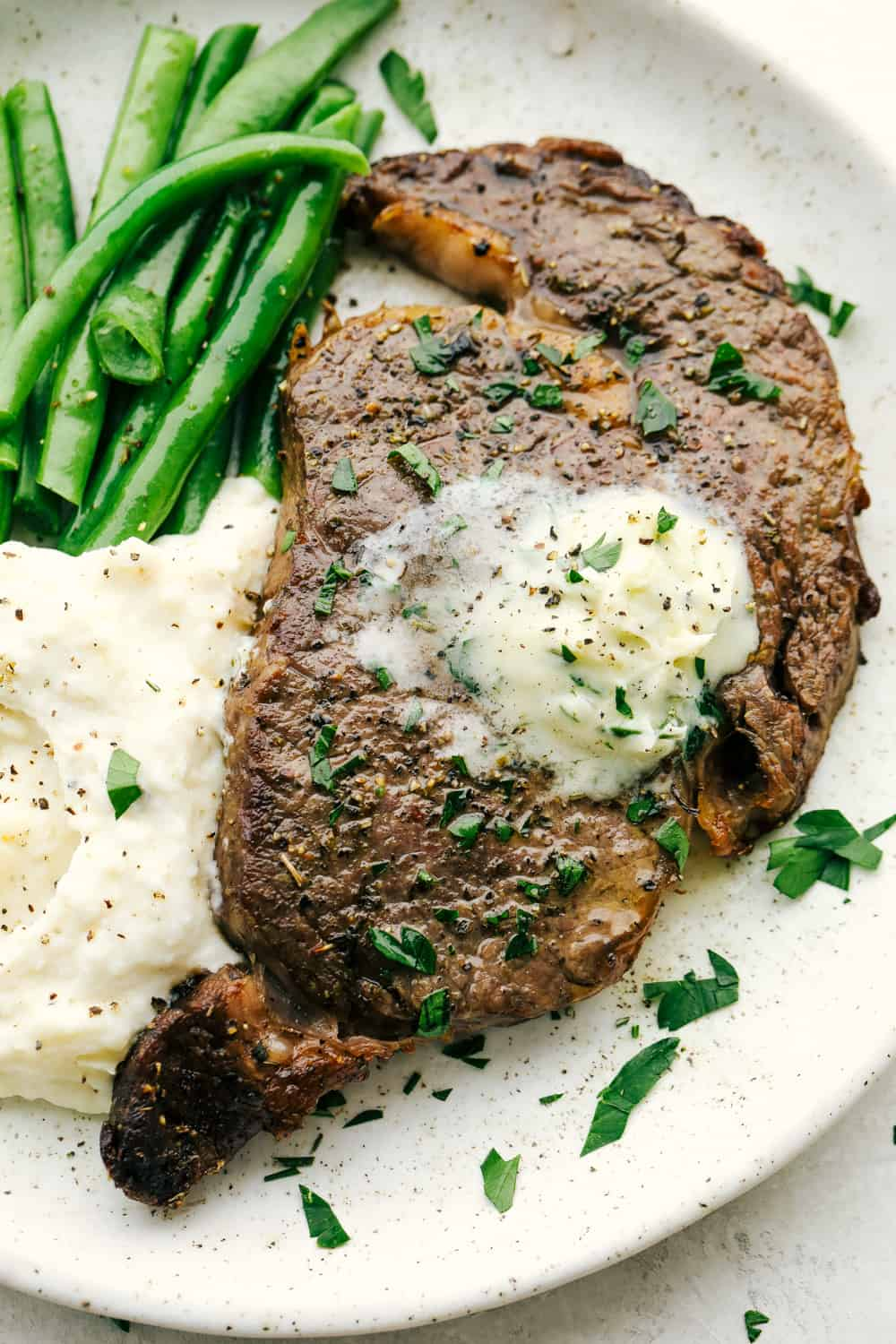 Perfect Air Fryer Steak with golden seared outside and tender juicy inside. Topped with garlic butter and a side of beans and potatoes.