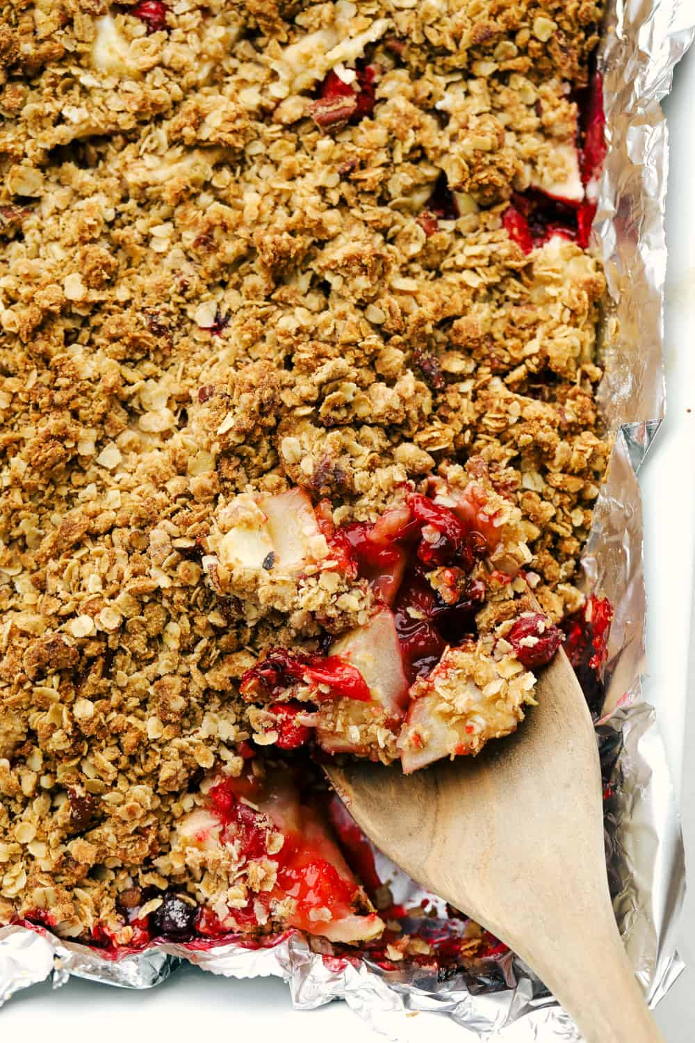 Cranberry apple crisp in a baking pan with a wooden spoon taking out a scoop.
