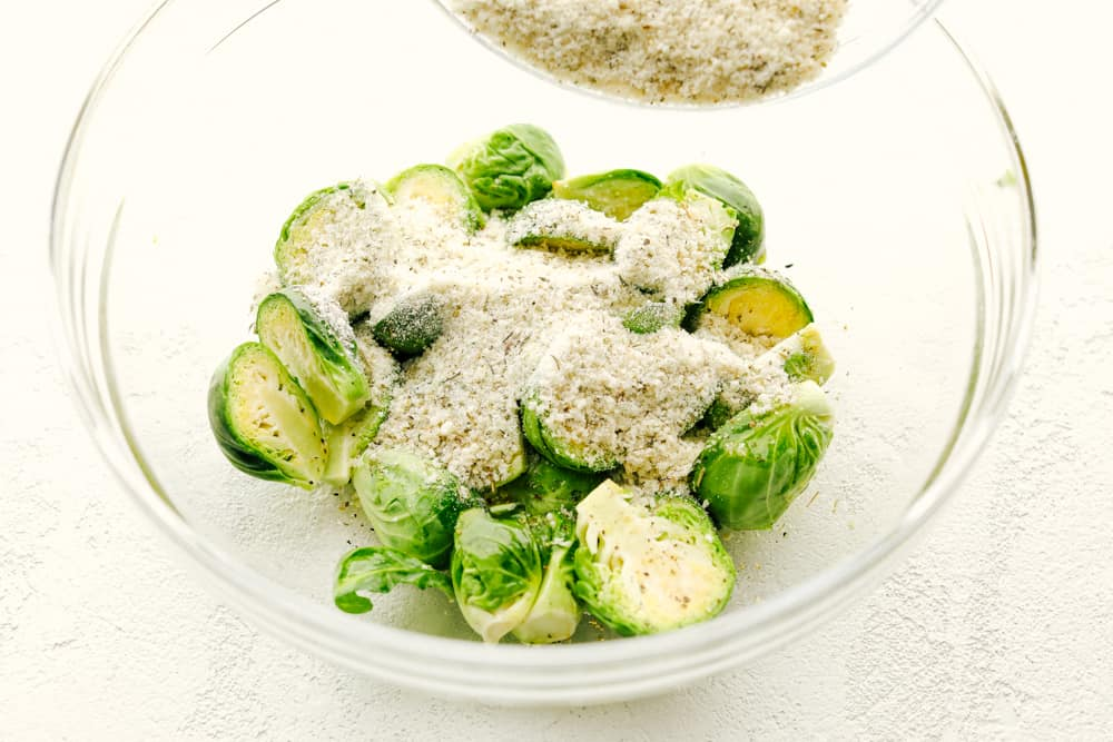 Coating the brussel sprouts with parmesan and seasonings.