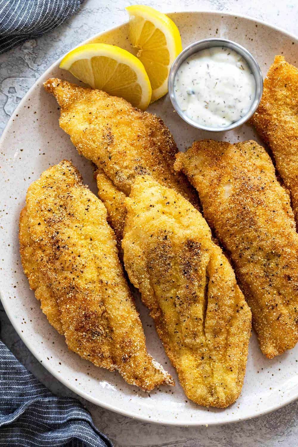 Fried Catfish on a white plate with two lemon slices.
