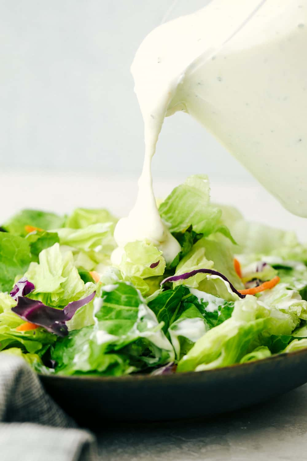 Pouring rich, creamy zesty Homemade Ranch Dressing on Salad.