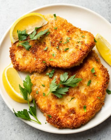pork schnitzels on a plate with lemon wedges