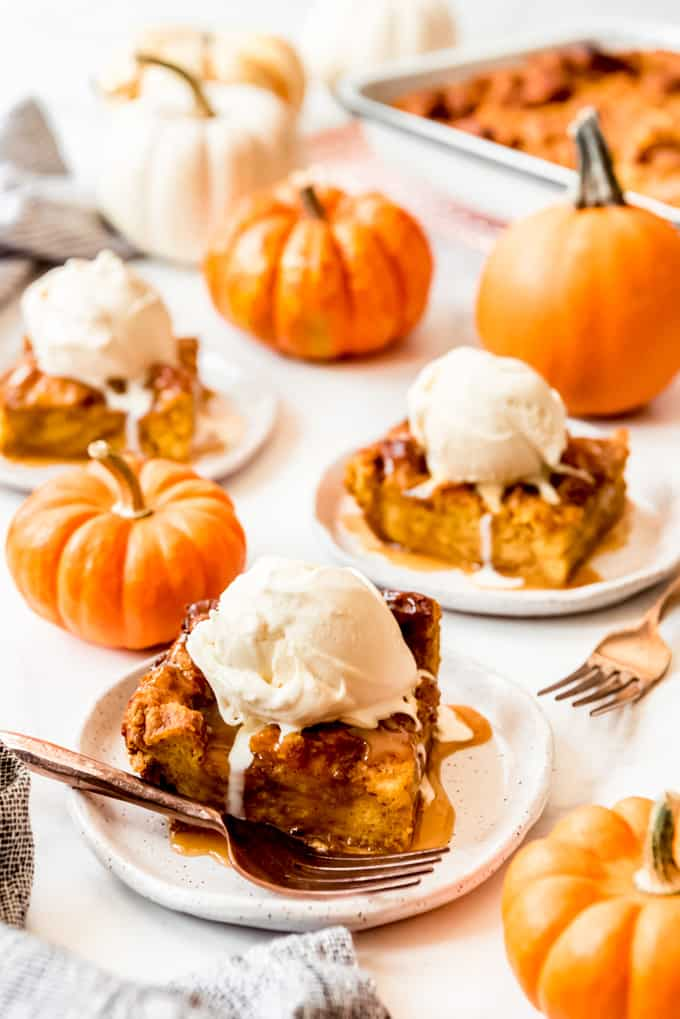 Slices of pumpkin bread pudding with ice cream on top.