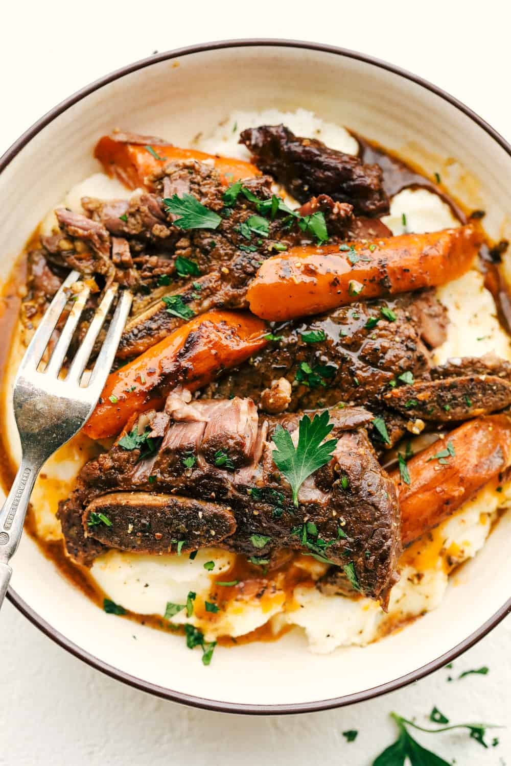 Fork Tender Slow Cooker Short Ribs in a bowl with mashed potatoes and carrots.