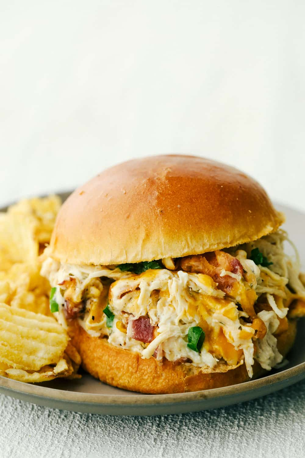 Creamy, rich addicting Slow Cooker Crack Chicken with cheddar, bacon and ranch on a bun.