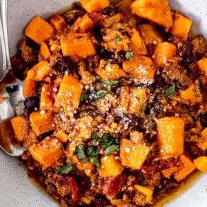 Sweet potato chili in a large bowl topped with parmesan cheese and parsley.