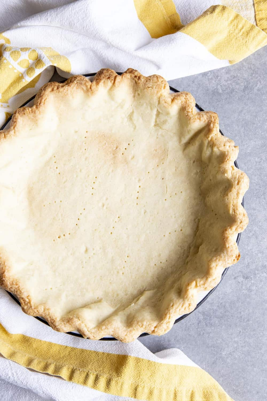 A par-bake pie crust on a gray surface next to a tea towel
