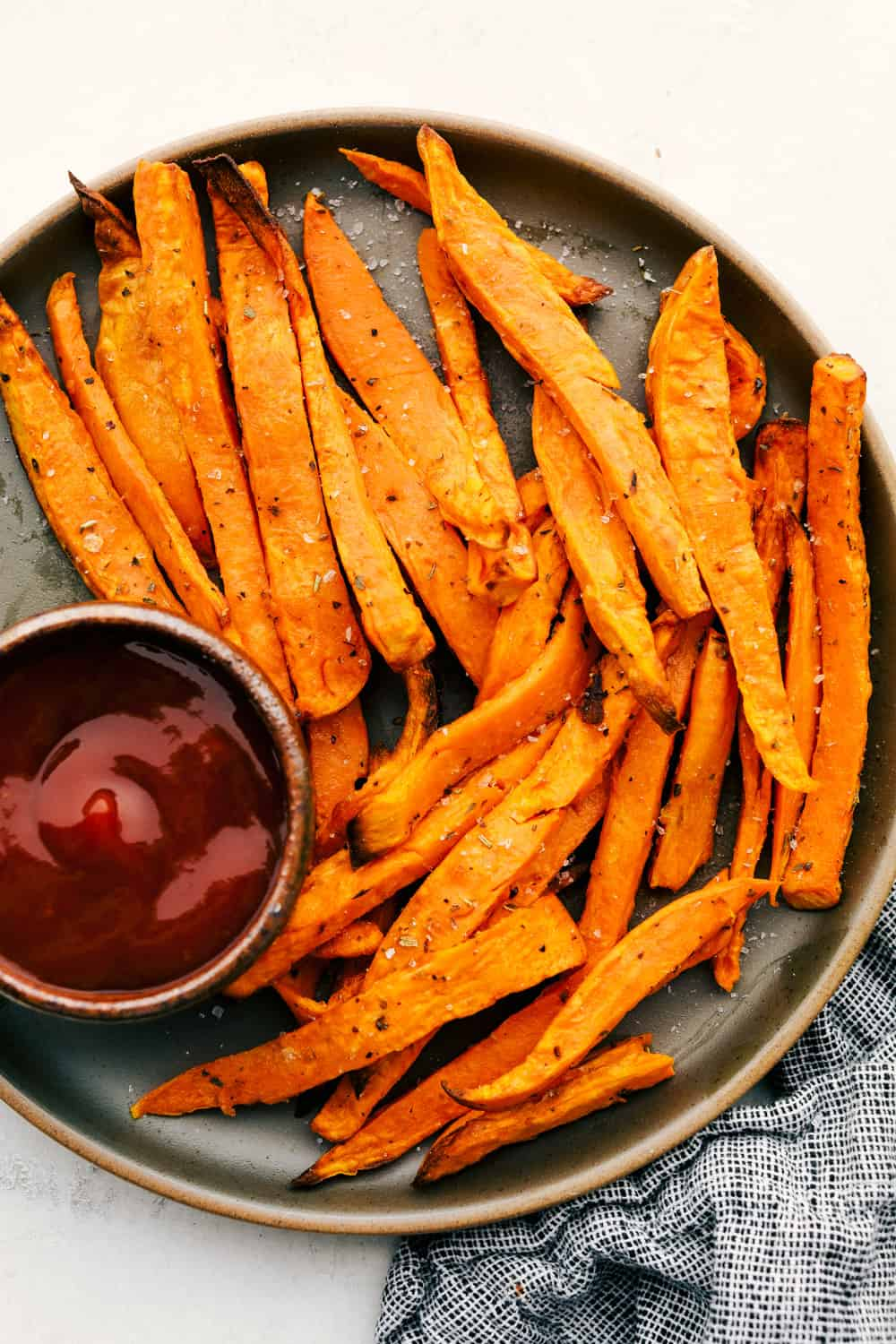 Sweet potato fries on a plate with sauce for dipping.