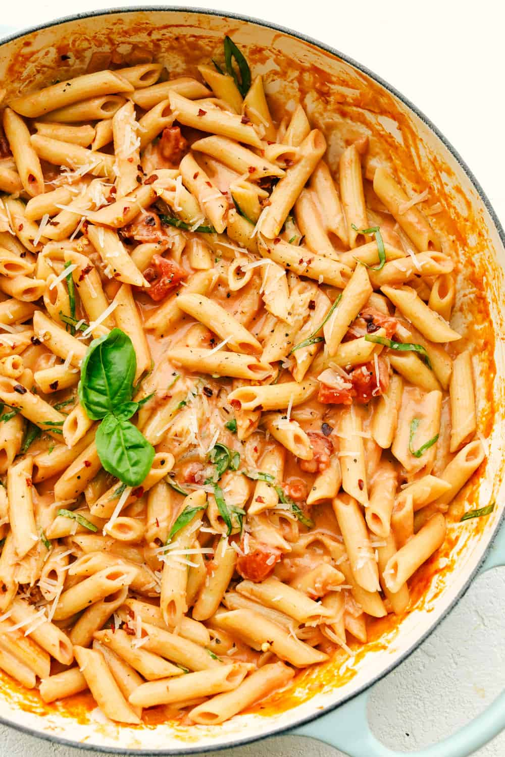 Creamy Penne Alla Vodka in a pot, with basil.