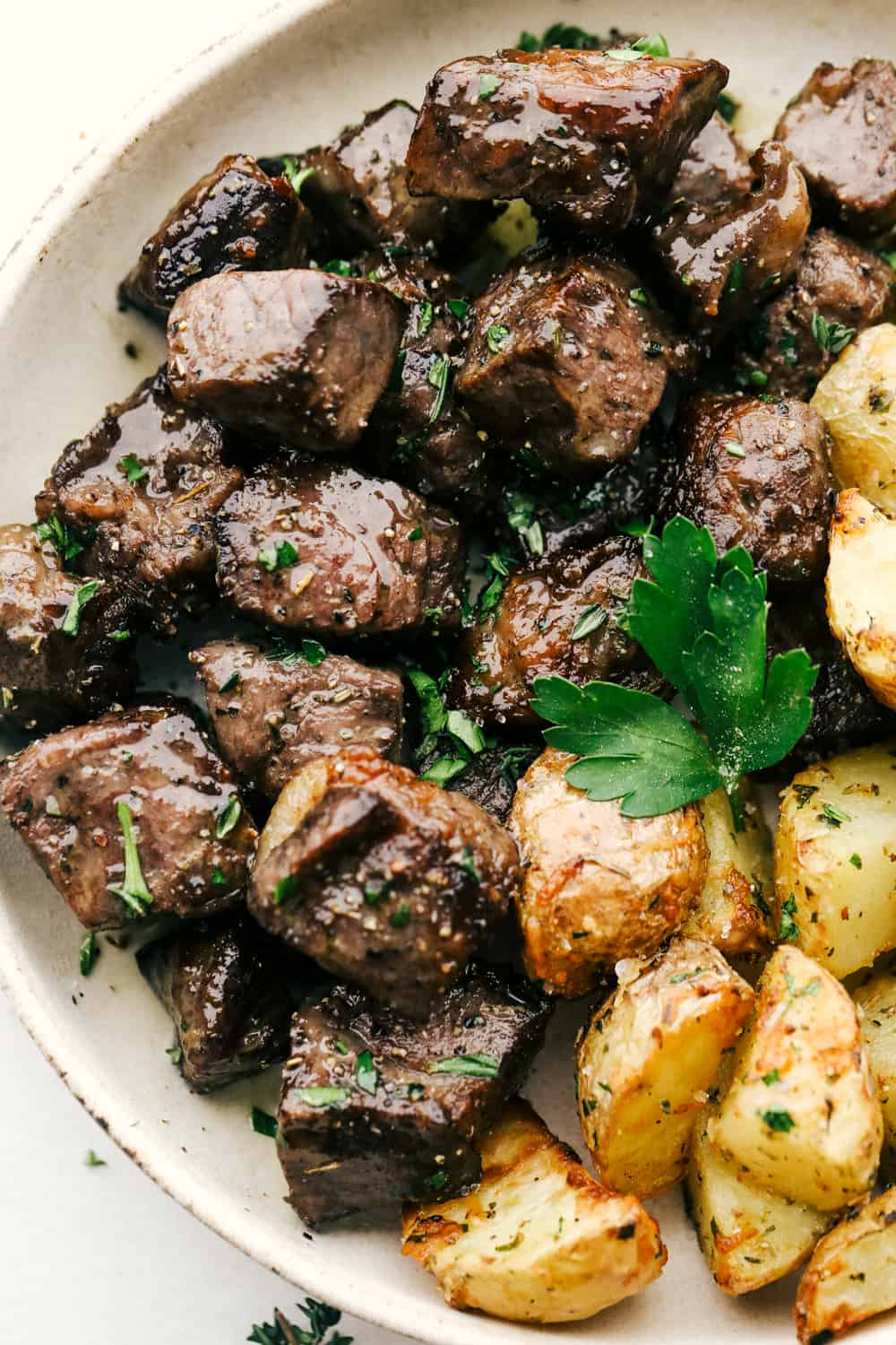 Air Fryer steak bites with roasted potatoes on a plate.