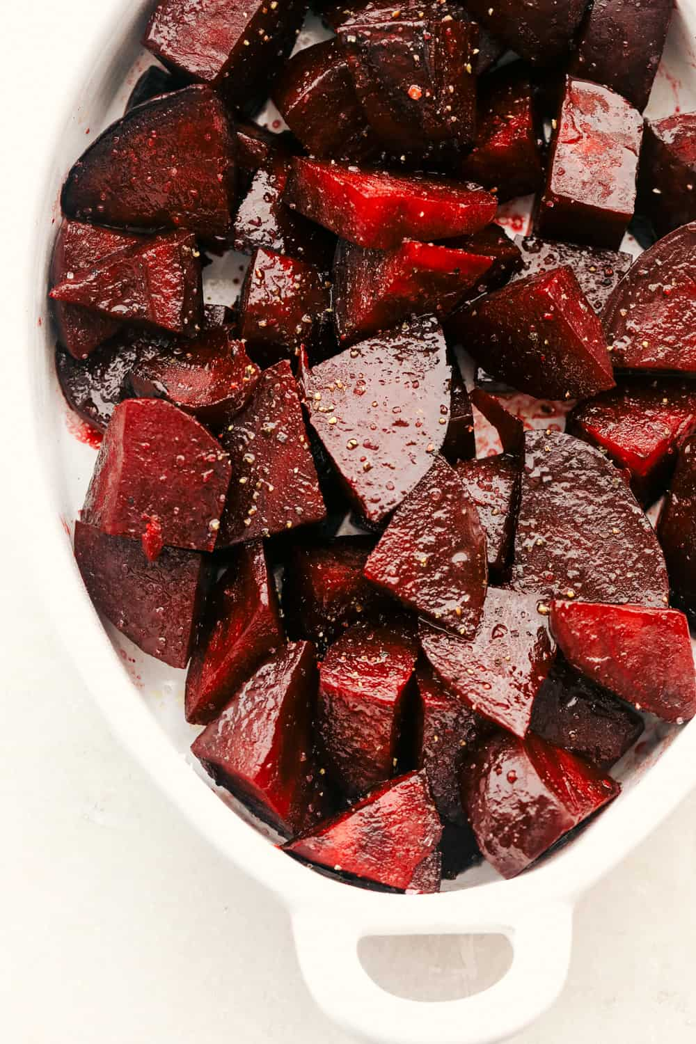 Seasoned beets in a roasting pan.