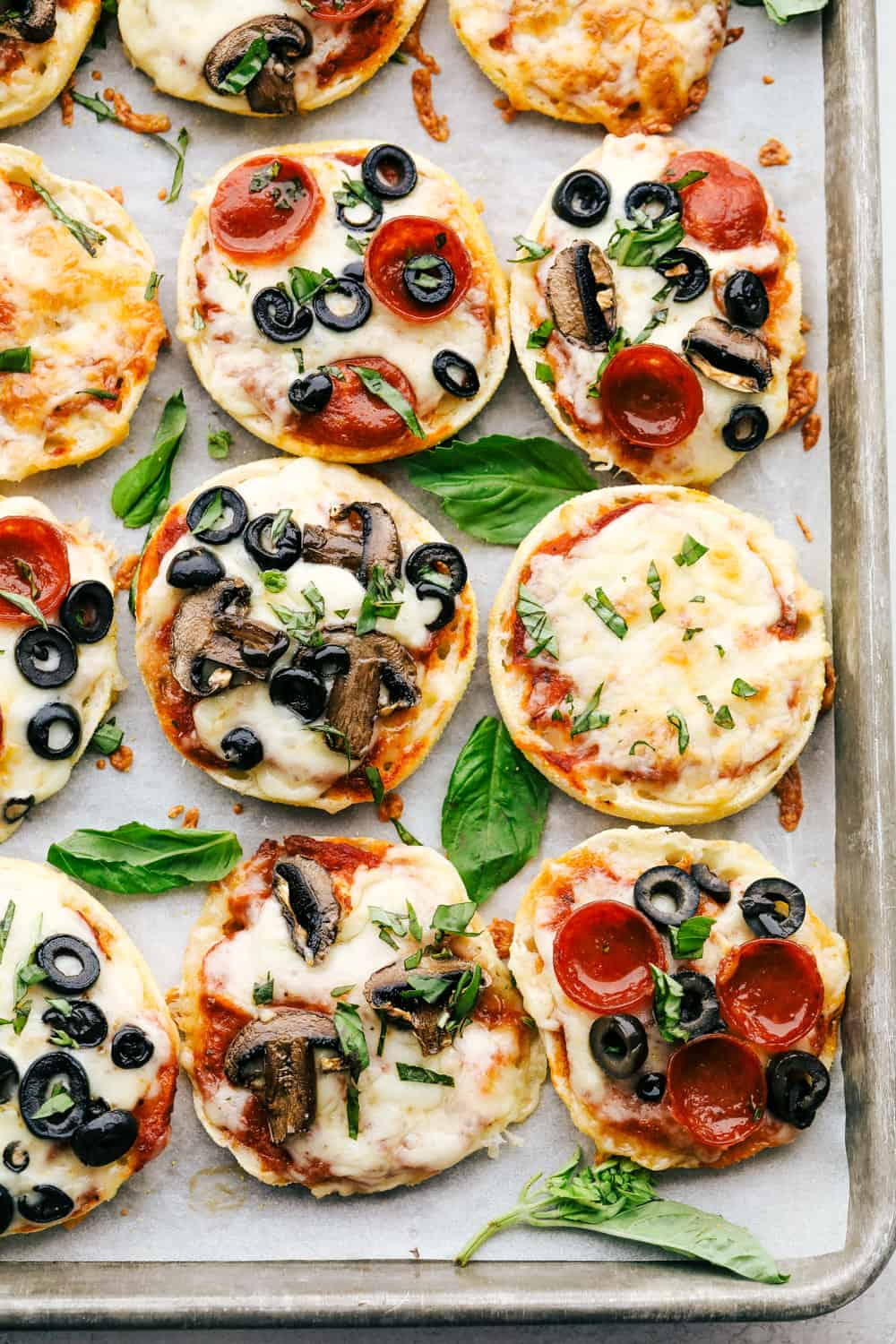 Toasty and perfect english muffin pizzas on a cookie sheet.