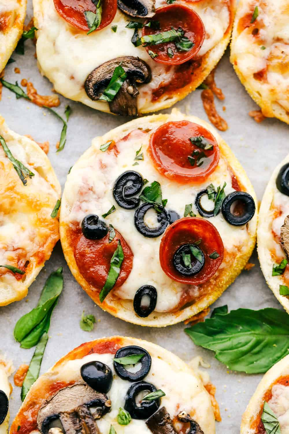 English muffin pizza topped with olives and pepperoni.