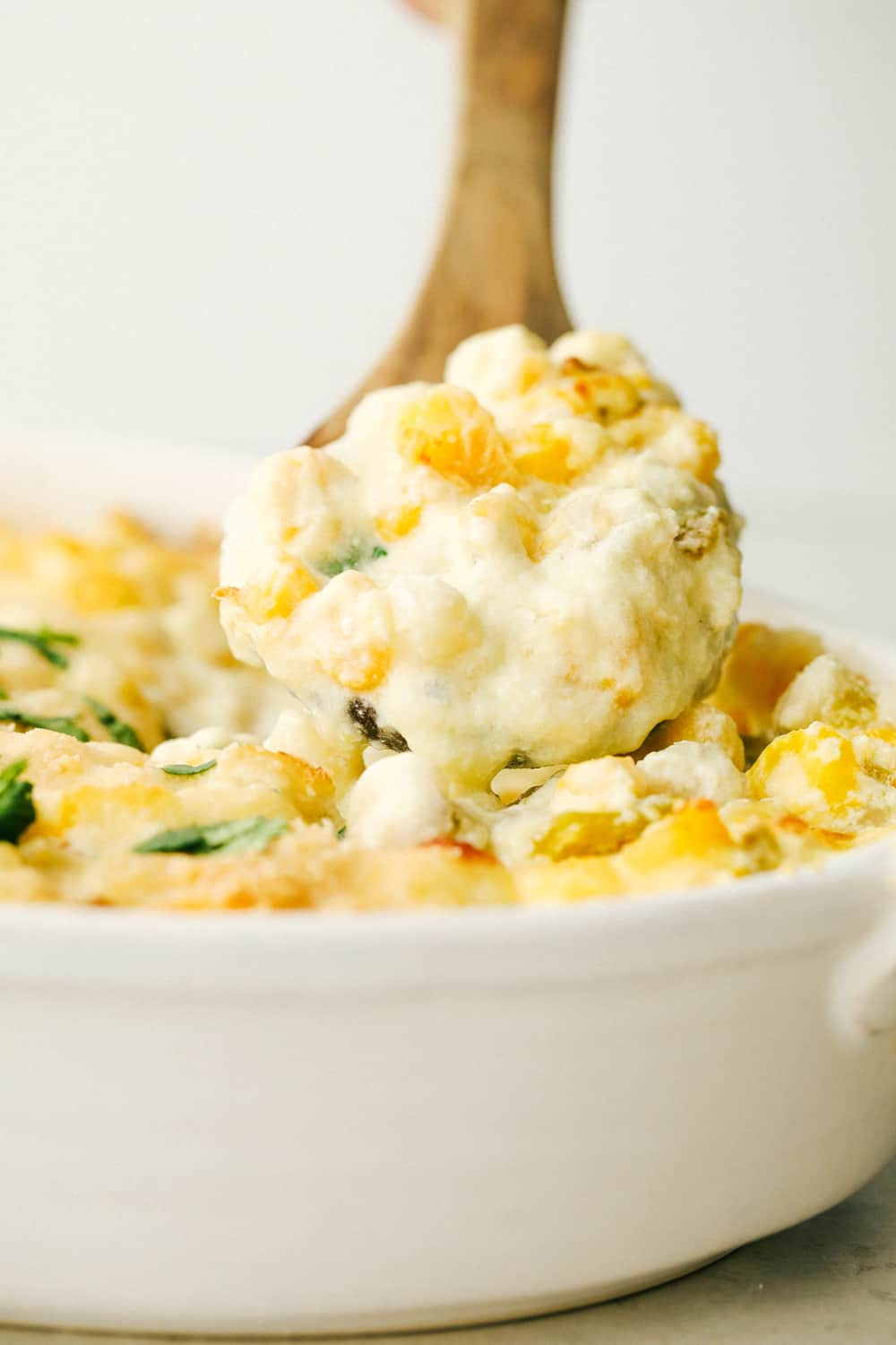 Scooping out creamy cheesy hominy casserole.