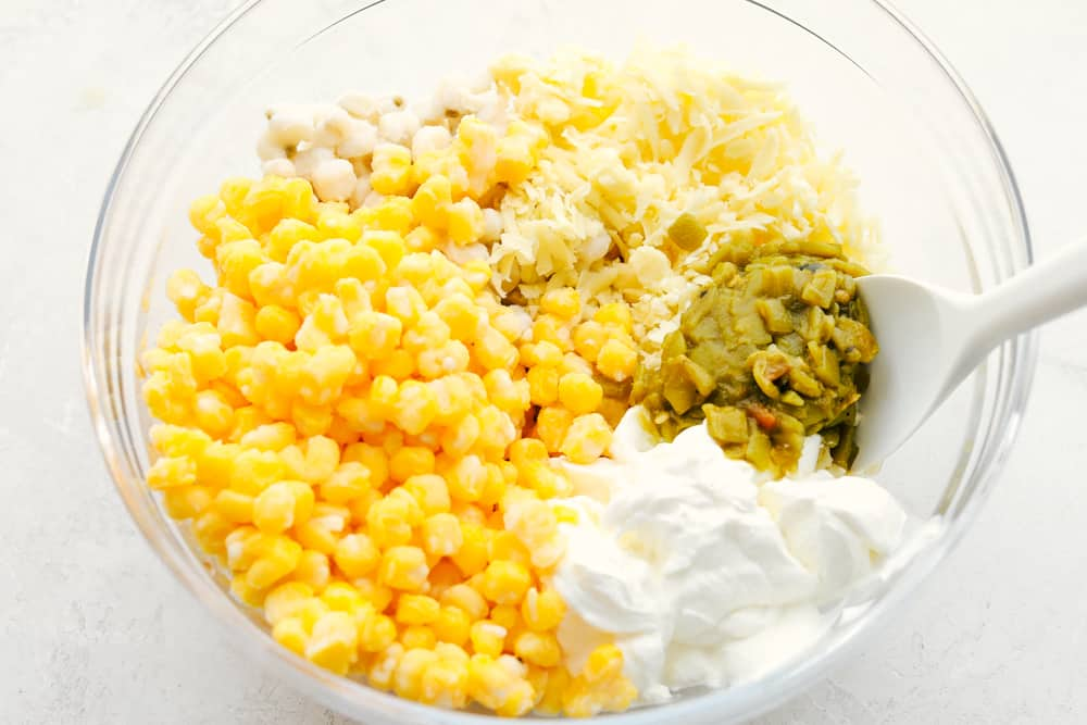 Ingredients for hominy casserole in a glass bowl.