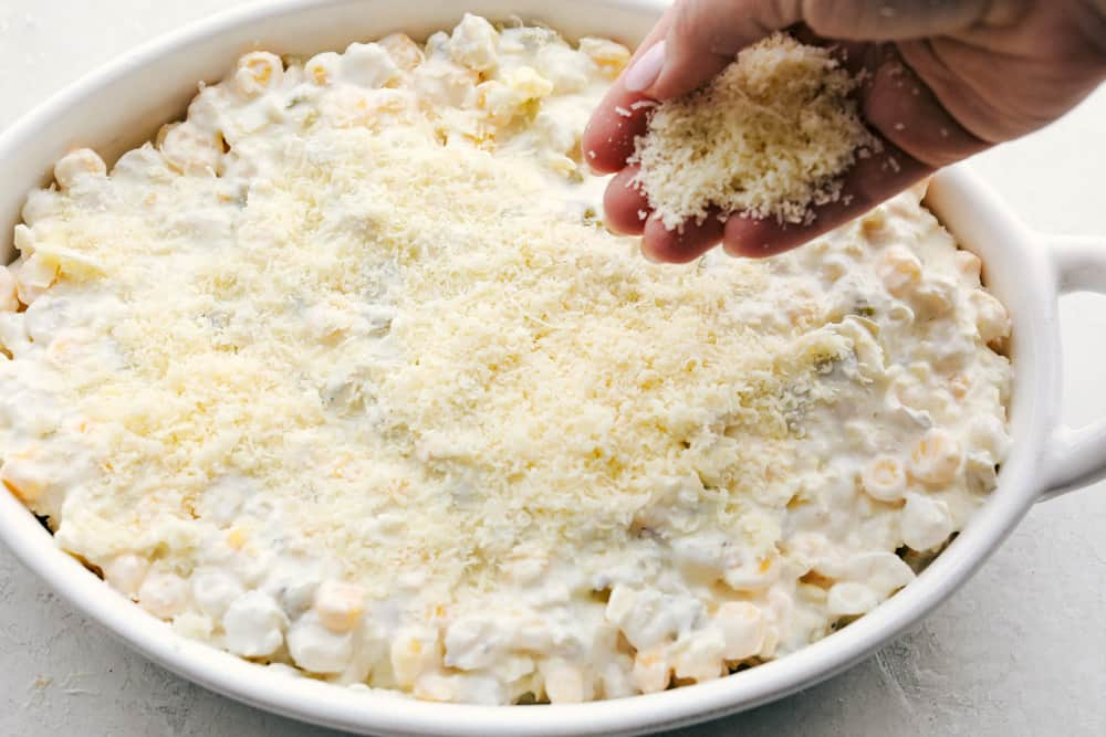 Putting the cheese topping on top of hominy casserole.