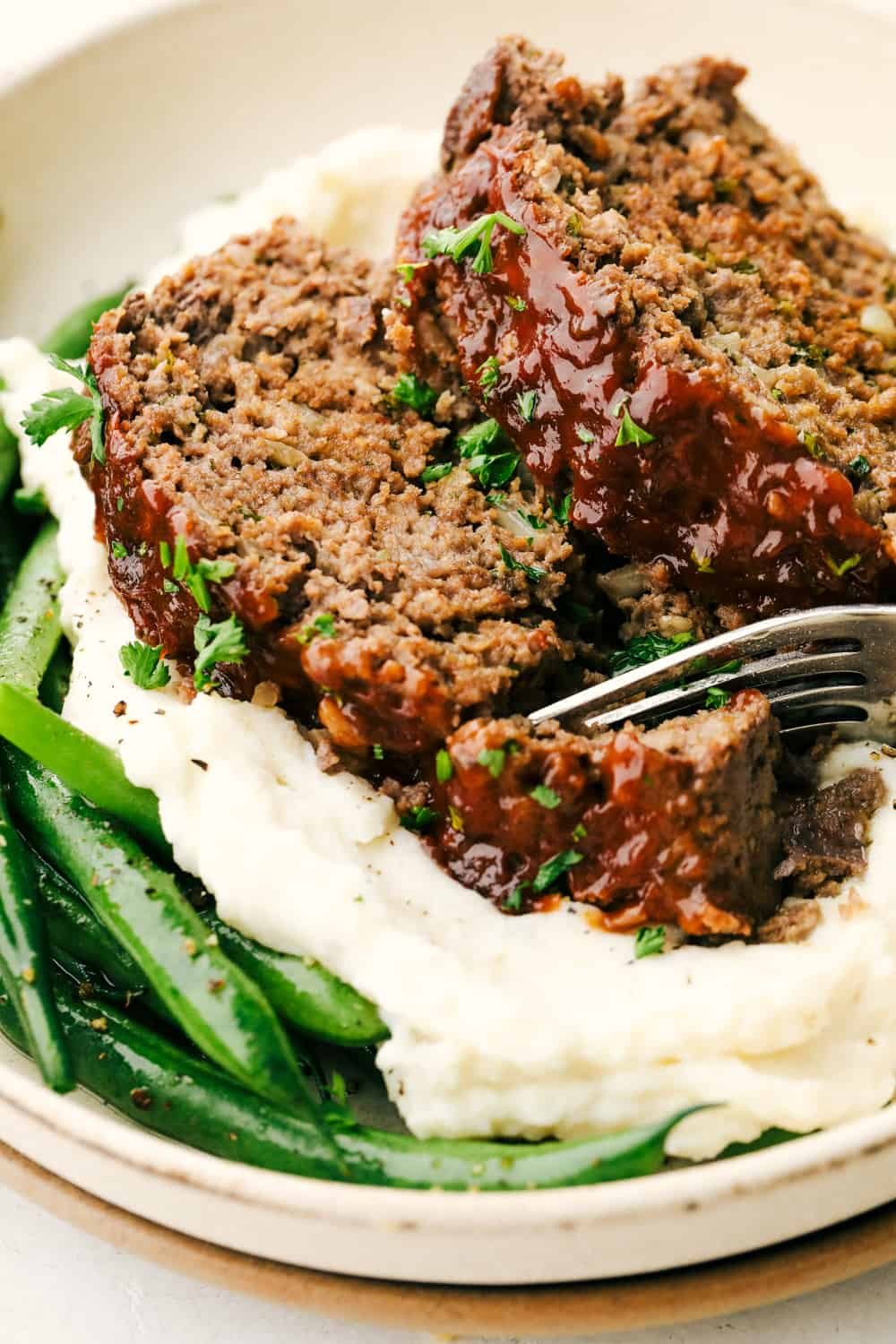 Tender and juicy meatloaf on a bed of mashed potatoes and green beans.