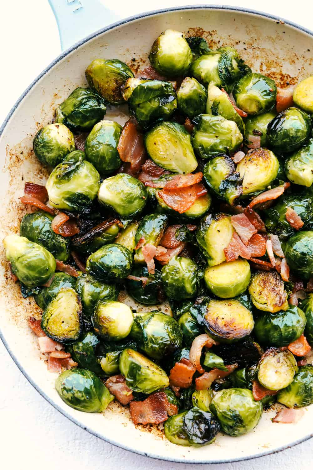 Brussel sprouts with bacon and maple syrup in a white bowl.