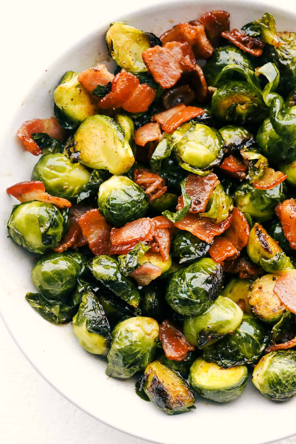 Bacon, brussel sprouts tossed with maple syrup on a white plate.