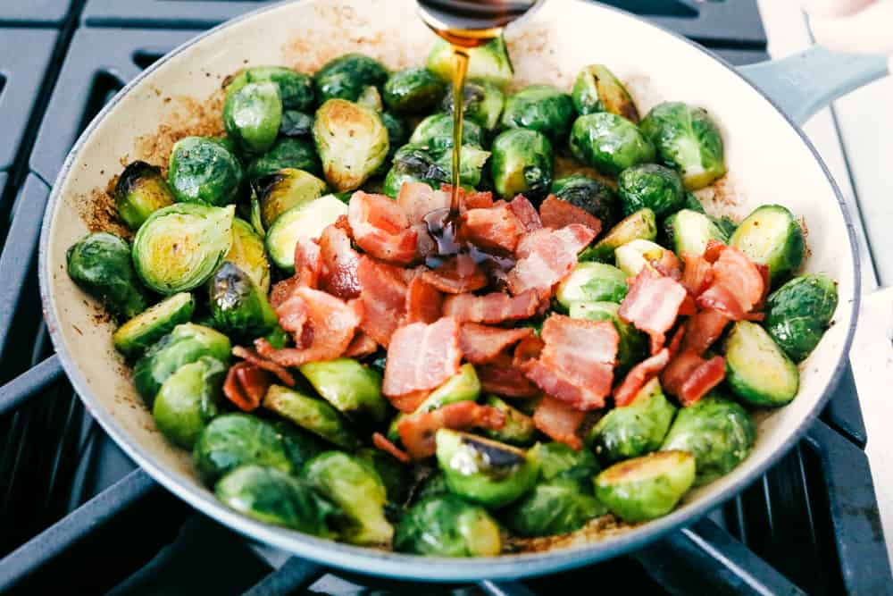 Pouring the maple syrup over the brussel sprouts and bacon.