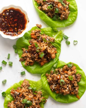 Overhead picture of chicken lettuce wraps with sweet chilli sauce on the side