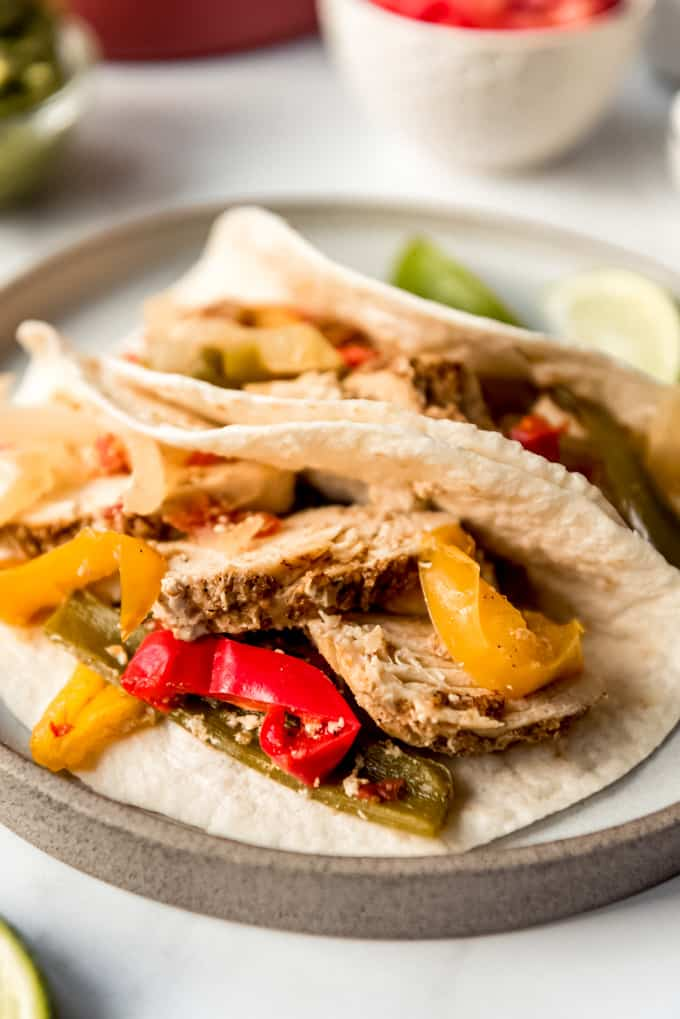 Crockpot chicken fajitas on tortillas on a plate.