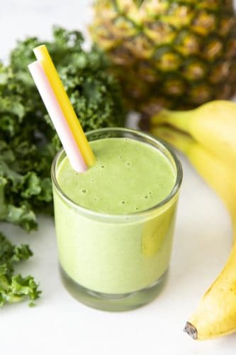 Kale smoothie in a glass surrounded by bananas, kale and pineapple