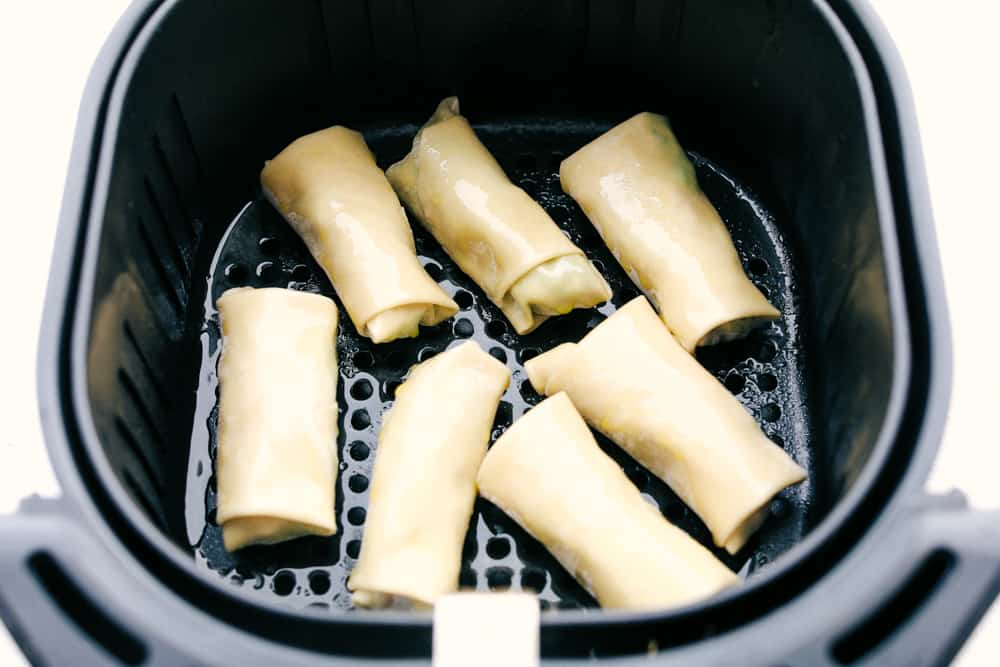 Air fryer basket filled with avocado egg rolls for frying.