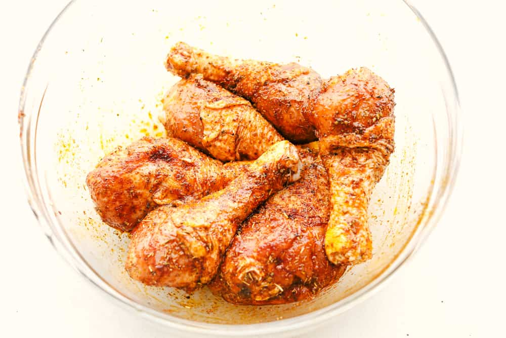 Seasoning chicken legs for the air fryer.