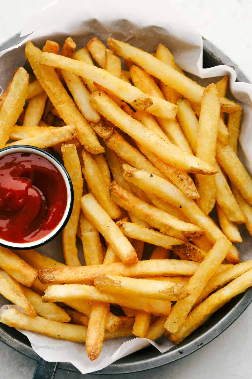 French fries on a plate with ketchup.