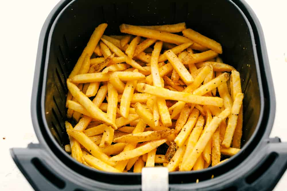 Up close picture of french fries in air fryer basket.
