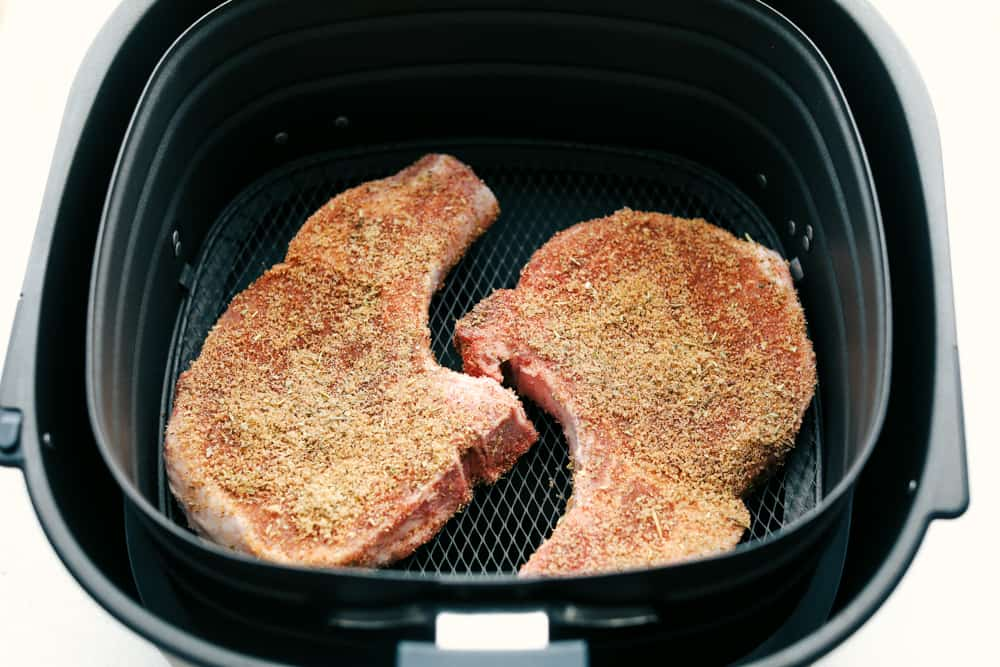 Seasoned pork chops in the air fryer basket.