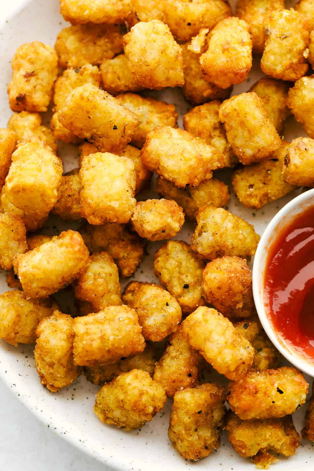 Perfect air fryer tater tots on a plate with ketchup.