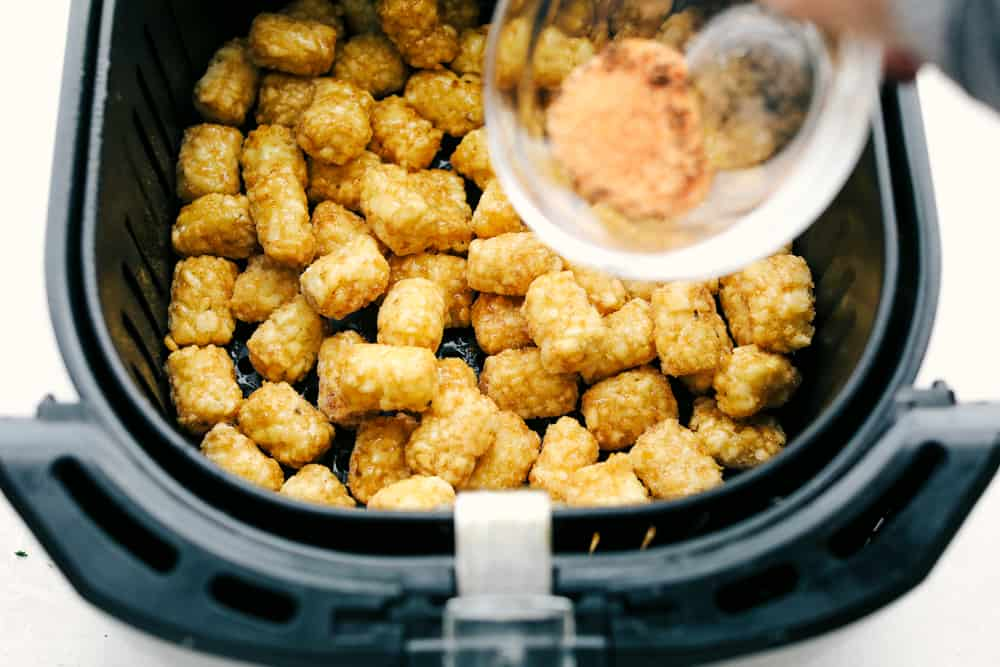 Seasoning frozen tater tots in the air fryer.