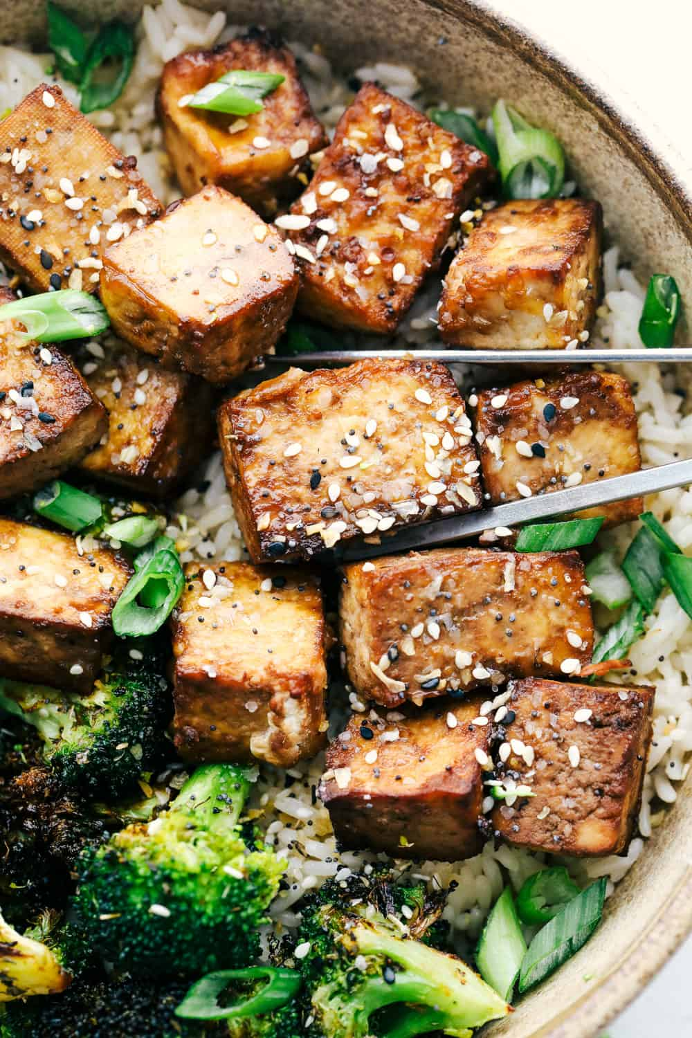 Using chopsticks to pick up air fried tofu with rice and broccoli.