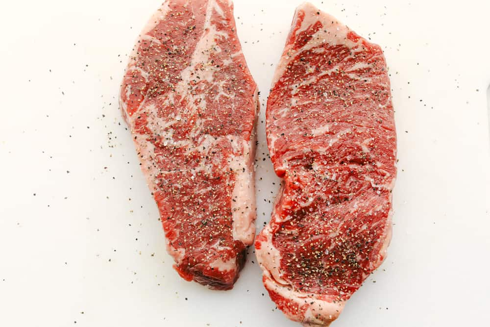 Two steaks seasoned with salt and pepper.