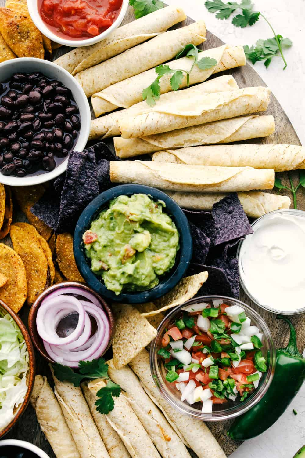 Taquitos on a board with bowls of dips, vegetables and chips all around.