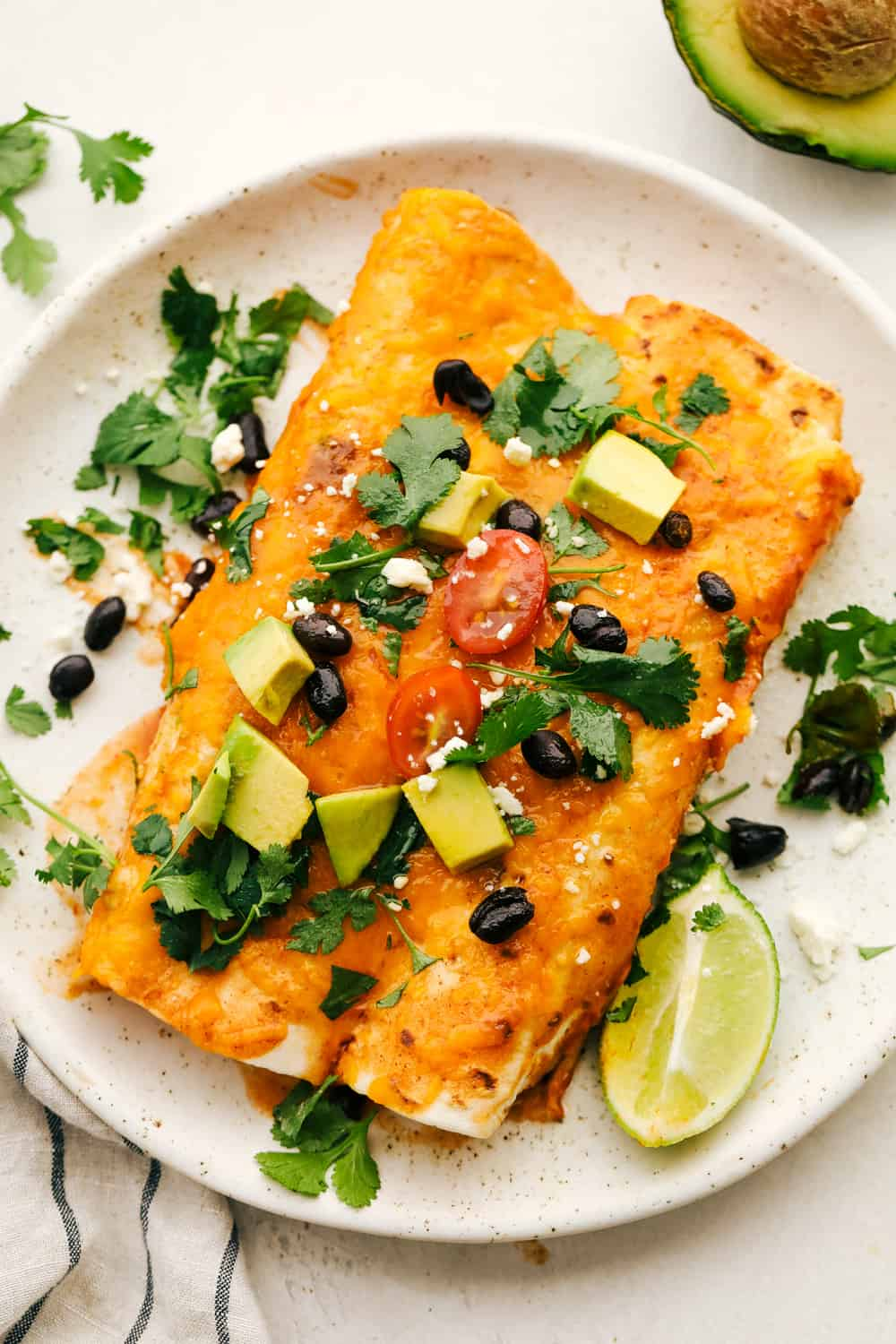 Two black bean and sweet potato enchiladas on a white plate with optional toppings.